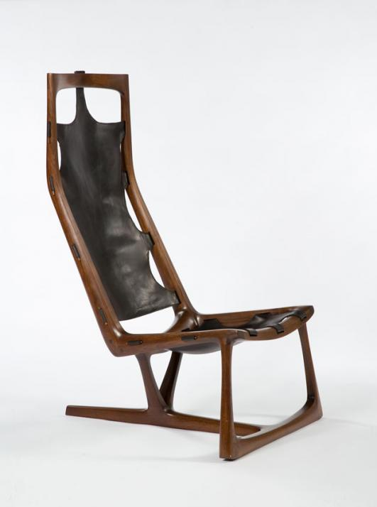 "Early ""Kangaroo"" chair in hand-carved walnut and slung leather. Designed and made by Wendell Castle, Rochester, New York, 1962. Signed and dated, WC 62. One of the first three chairs produced by Wendell Castle."